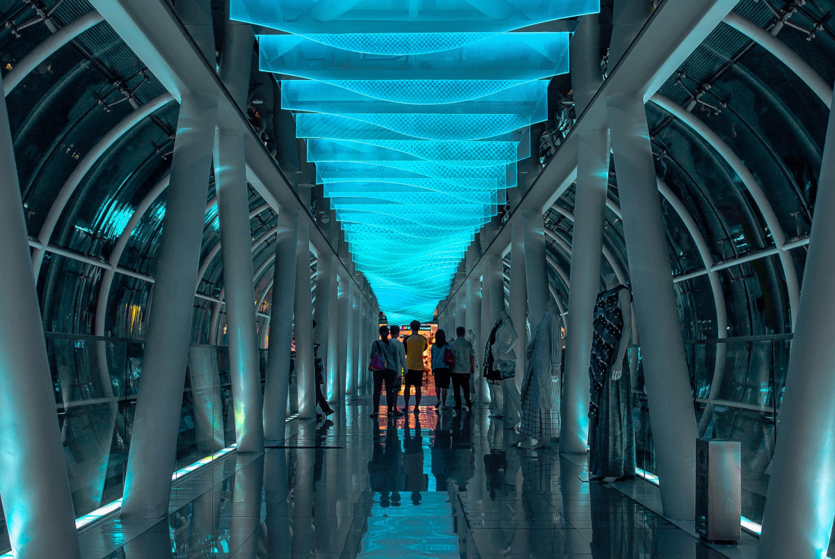 People in a hallway with blue lighting - Photo by Lily Banse on Unsplash